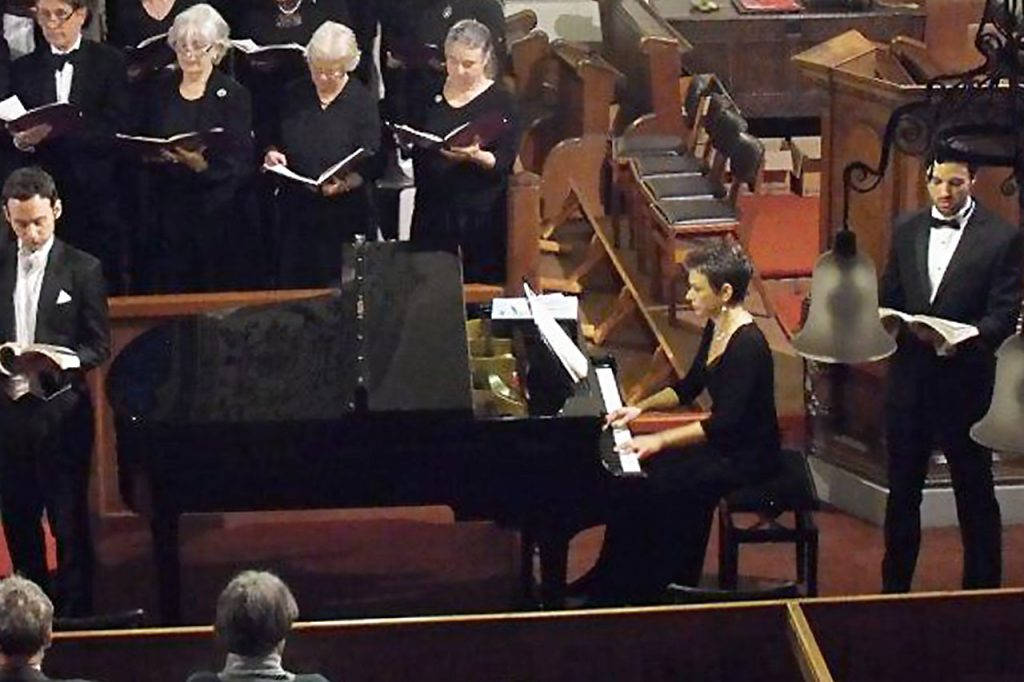 playing piano at concert with choir and soloists